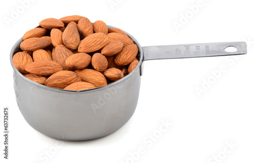 Whole unblanched almonds in a metal cup measure