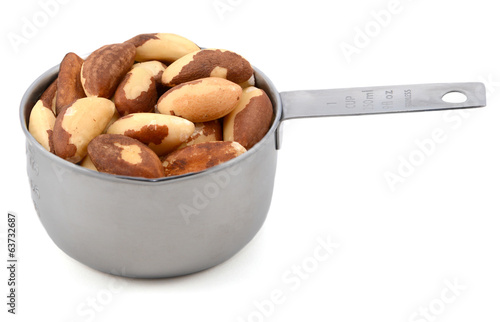 Whole brazil nuts in a metal cup measure