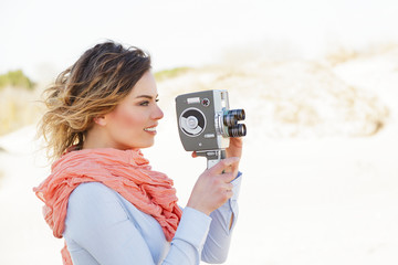 Outdoor Portrait of young woman holding vintage 8mm camera