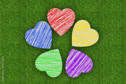 Colorful marker drawing hearts over green grass background