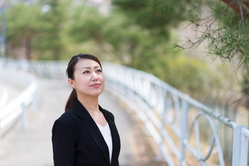 自然の中でリフレッシュするアジアのスーツの女性