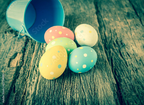 Easter eggs with pail on wood