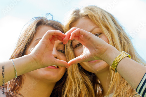 Two girls with finger heart