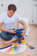 a young man sitting on floor holding paint roller and looking on