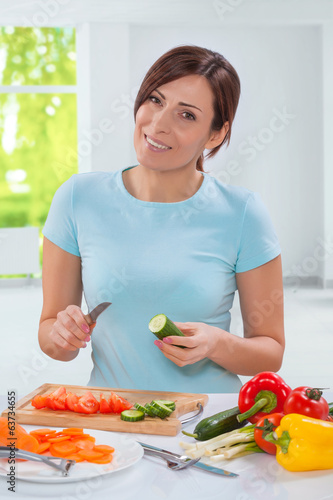 beautiful smiling caucasian model holding cucumber with kitchen