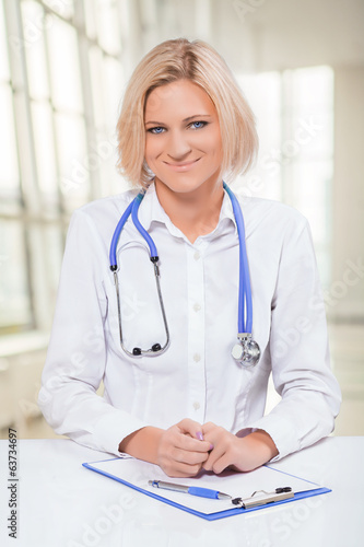 beautiful smiling female doctor sitting at white table and  look