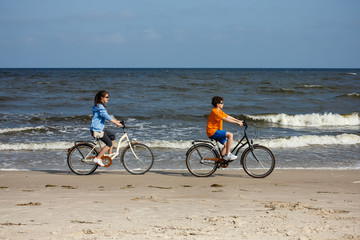 Teenage girl and boy biking on beach