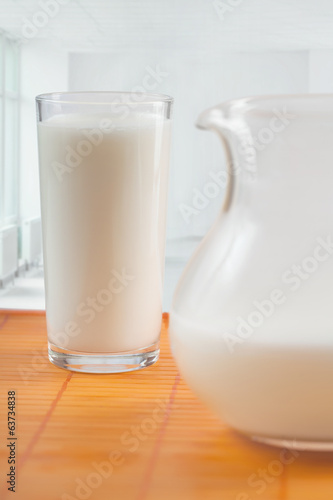 The jug and glass with milk stand on a table
