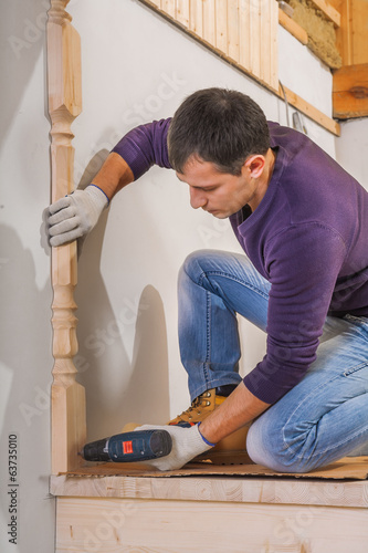 young carpenter fixing wooden post with cordless drill
