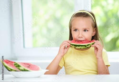Cute little girl is eating watermelon