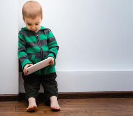 Маленький мальчик с планшетным компьютером в руках