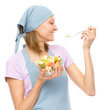 Young attractive woman is eating salad using fork