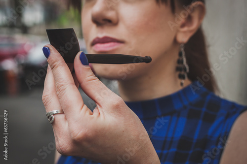 Detail of a pretty girl smoking vintage pipe