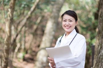緑のある自然の中で仕事をする女医