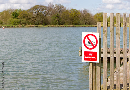 No swimming sign on jetty at edge of lake