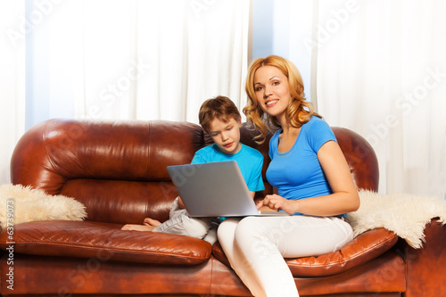 Child looking at laptop with smiling mum