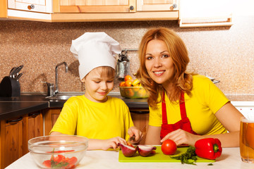 Boy as chef cutting vegetables with mother
