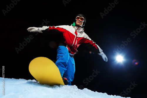 Young man wearing ski mask balancing on snowboard