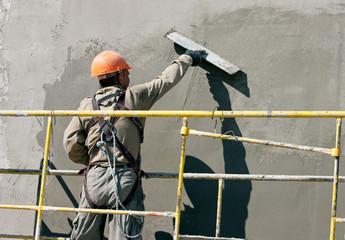 Plasterer worker during finishing facade works