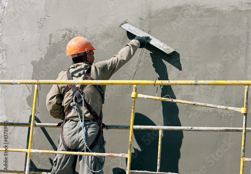 Plasterer worker during finishing facade works