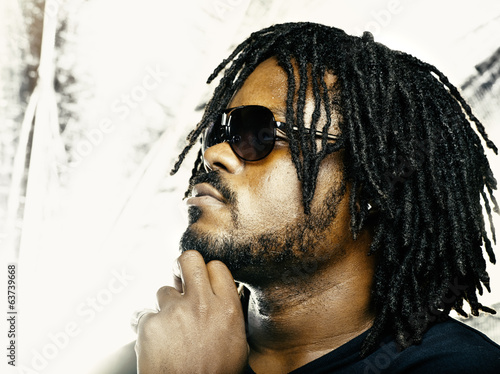 funky guy with dreadlocks and sunglasses thinking