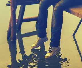 Legs of teenager sitting on the wooden dock