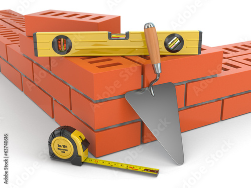 Construction concept. Brick wall trowel and level,