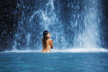 woman refreshing in waterfall in bali