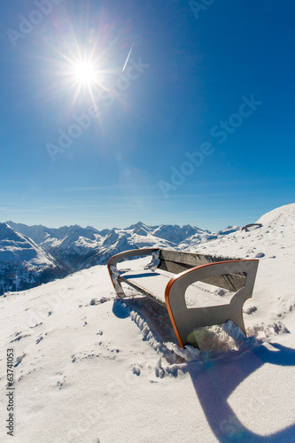 Bench in ski resort Bad Gastein in snowy mountains, Austria