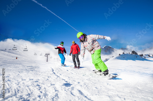 Guys and one man snowboarding downhill