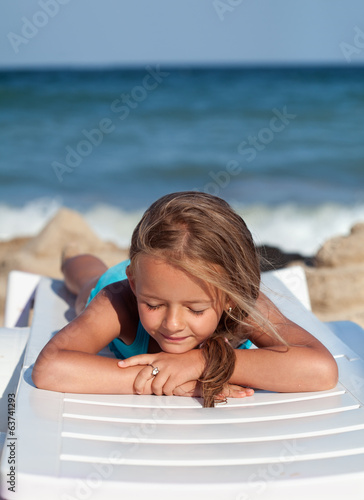 Little girl relaxing on a beach chair