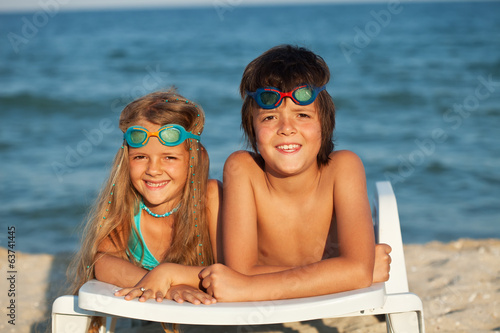 Kids laying on beach chair wearing swimming goggles