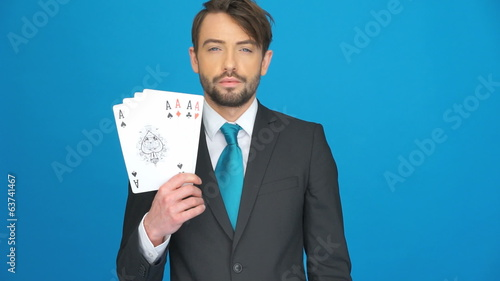 handsome businessman holding playing cards on blue