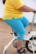 Постер, плакат: overweight woman exercising on bike simulator