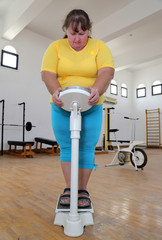 women with overweight on scales in gym