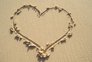 Drawing heart on sand beach.