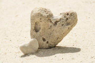 Couple of hearts on white sand beach.