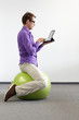 canvas print picture - man on stability ball with tablet,correct sitting position