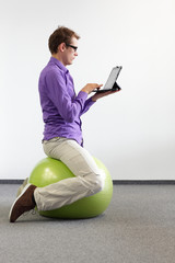 man on stability ball with tablet,correct sitting position