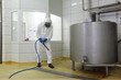 worker ,high pressure washer,  cleaning floor in plant