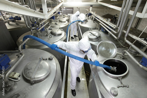 workers with blue hoses, filling large silver tanks i