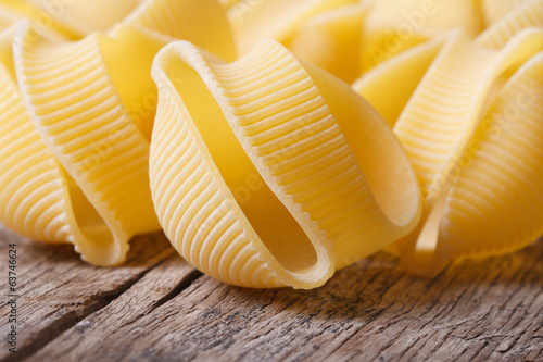 Raw Italian macaroni lumaconi scattered on the old desk