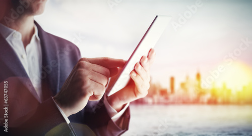 Man with tablet computer and city on horizon