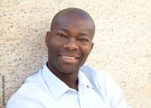 African man on a wall lokking at camera