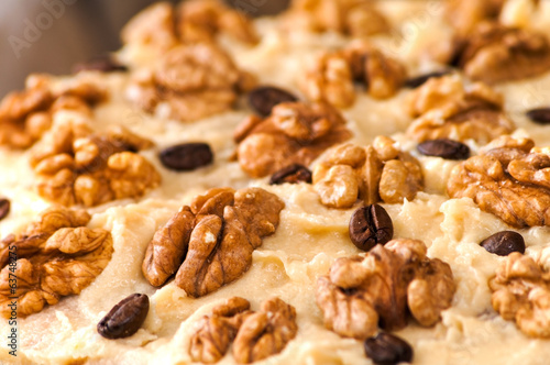 close up view of cake with walnuts and coffee beans