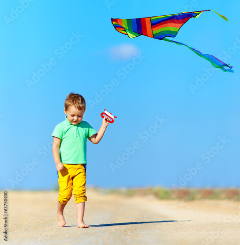 cute barefoot kid playing kite on vacation