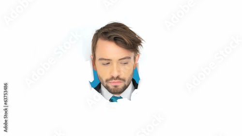 businessman looking arround true paper hole