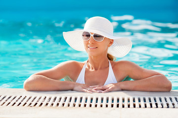 Young beautiful woman enjoying the sun in the pool.
