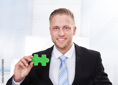Successful businessman holding a puzzle piece