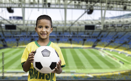 Brazilian little boy holds a soccer ball on the stadium